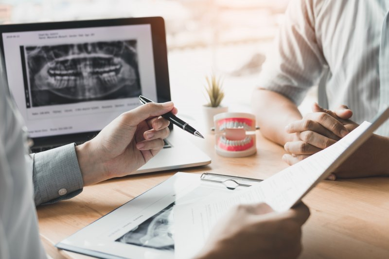 Dentist reviewing paperwork with patient